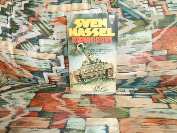 "Colored photograph of front cover of Sven Hassel's book 'Assignment Gestapo"" which has author's name in yellow capitals at top and title in orange capitals beneath., then a picture of a German tank. Book is on a colorful abstract background. Sven or Sajer."