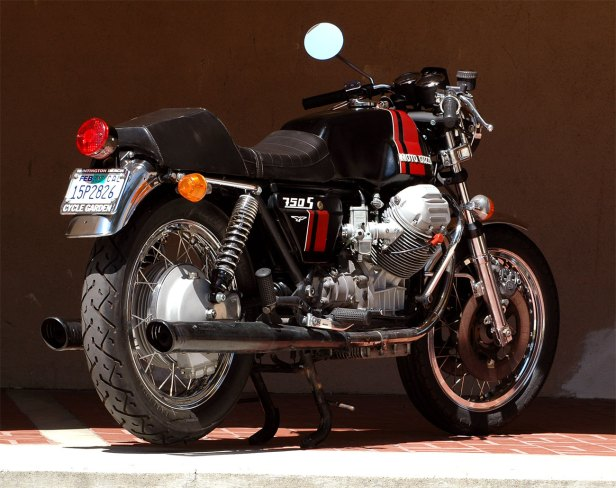 Colored photograph from rear 3/4 of Moto Guzzi motorcycle with black tank with red stripes.