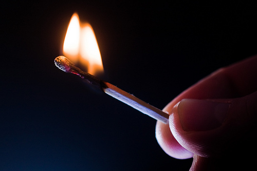 Finger tips are visible holding a burning match