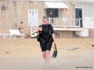 Diane Traffas walks in the rain from the SCUBA desk to the boat