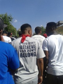 "This student, while marching to COSATU House wears a t-shirt in protest, that reads, ""If you don't believe, you don't belong"" Photo: Aarti Bhana"