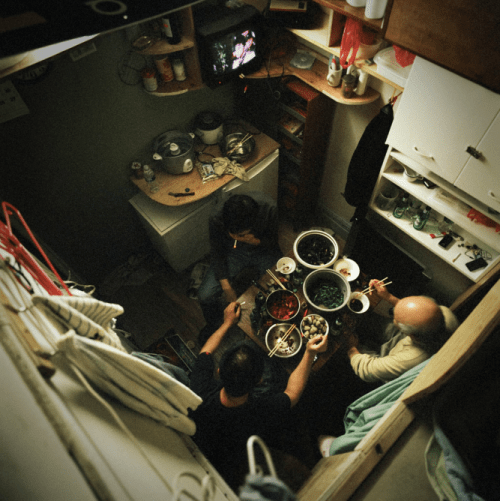 Former-residents of 81 Bowery cook and eat together in their tiny cubicles. | Credit: Annie Ling