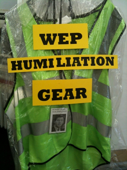 """The """"uniform"""" of some WEP workers, with added commentary and a badge featuring HRA Commissioner Robert Doar. At a recent action, CVH members presented Commissioner Doar with this vest and badge, which he refused to accept."""