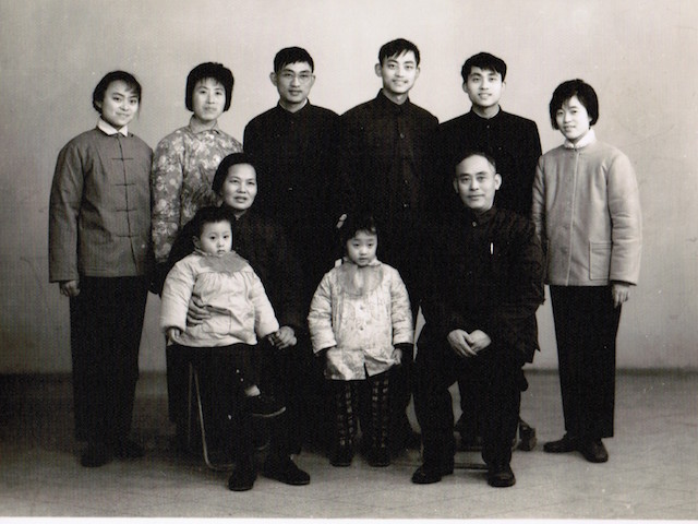 I was four years old, and my brother was three. The back row from left to right: my auntie, my parents, my younger uncle, my older uncle and his newlywed wife. My grandparents sat in the front row. My brother wanted to run away, so my grandma put him on her lap and held his hand. I was the good girl, furtively playing with my coat and exploring my pocket. Photo courtesy the author.