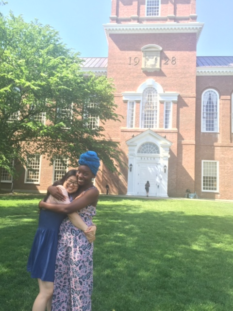 Margarita and Calin hug on a lush green lawn in front of the Dartmouth Baker-Berry tower. Their smiles are bright.