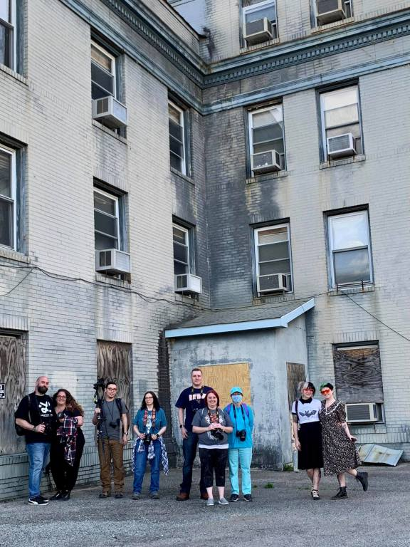 This is a group photo in front of an old hospital.