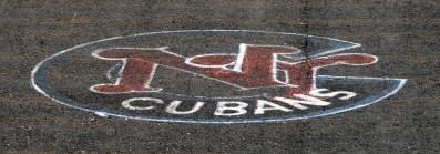 New York Cubans logo painted on asphalt surface of Hichliffe Baseball field