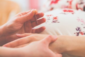Images shows a needle being inserted into a pregnant woman's hand.