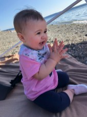 cute baby on beach clapping hands