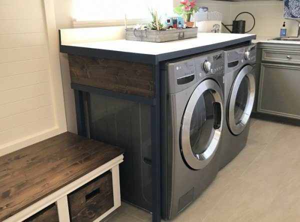 Build this DIY Laundry Table for just $85. This laundry table hides that ugly gap behind the machines, prevents things from falling behind the machines, and gives you a pretty place to fold that laundry.