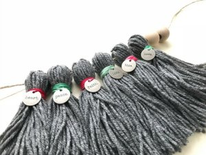 This DIY Yarn Tassel Garland is so easy to make. See easy to follow pictures and the how to video to follow along. Theme this to any holiday for Christmas Garland, Halloween, Easter, and more. #ChristmasGarland #YarnTassel #DIYYarnTassel #TasselGarland