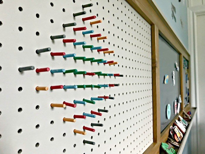 Colorful DIY pegs made from dowels in a painted pegboard. Build a fun DIY Modern Farmhouse Kids Activity Wall Board. With 20 Ideas for board options that work for kids, teens, and adults. #ModernFarmhouse #KidsFurniture #DIYKids #AbbottsAtHome