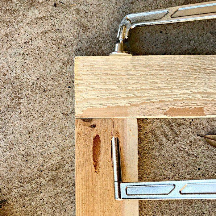 A Kreg Clamp in a pocket hole on a cedar 1x3 board. Build a fun DIY Modern Farmhouse Kids Activity Wall Board. With 20 Ideas for board options that work for kids, teens, and adults. #ModernFarmhouse #KidsFurniture #DIYKids #AbbottsAtHome