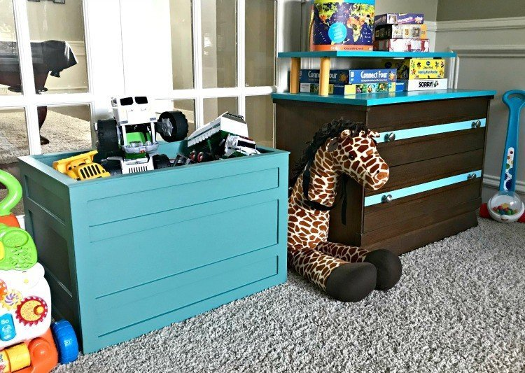 Kids playroom toy storage in a open DIY teal crate and a low dresser. Build a Modern Farmhouse DIY Wooden Toy Storage Crate or Box for all of those kids toys cluttering up your house. Makes a beautiful throw pillow and blanket box in a Living Room or catch all storage box for teens too! #AbbottsAtHome #StorageBox #ToyBox #DIYStorage