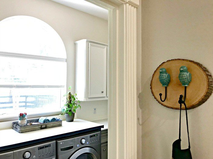 This DIY Wood Slice Wall Hook holds aprons. The Laundry Table I built to go over our washer and dryer adds extra style, storage and organization to this Laundry Room Makeover. This Modern Farmhouse DIY Laundry Room Makeover Ideas post is full of Before & After Makeover Photos, budget-friendly DIY ideas, and Laundry Room decor. #LaundryRoom #BeforeandAfter #AbbottsAtHome