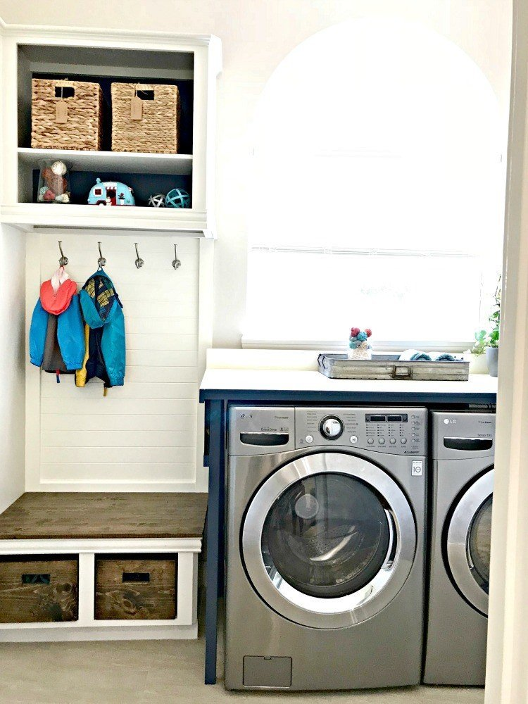 This mudroom bench and coat storage used to be a standard base cabinet and upper cabinet before she cut them in half. This Modern Farmhouse DIY Laundry Room Makeover Ideas post is full of Before & After Makeover Photos, budget-friendly DIY ideas, and Laundry Room decor. #LaundryRoom #BeforeandAfter #AbbottsAtHome