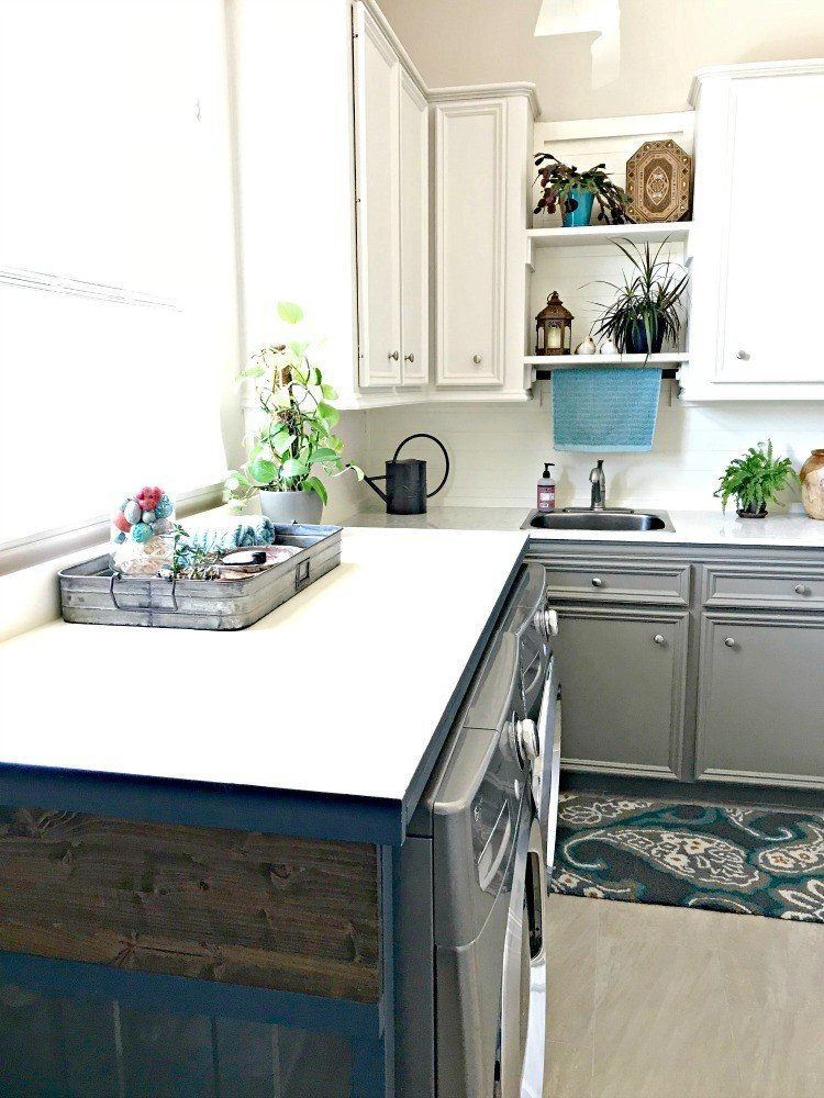 A DIY table over the washer and dryer hides the ugly machines and cords while adding extra style, storage and a place to fold laundry. This Modern Farmhouse DIY Laundry Room Makeover Ideas post is full of Before & After Makeover Photos, budget-friendly DIY ideas, and Laundry Room decor. #LaundryRoom #BeforeandAfter #AbbottsAtHome