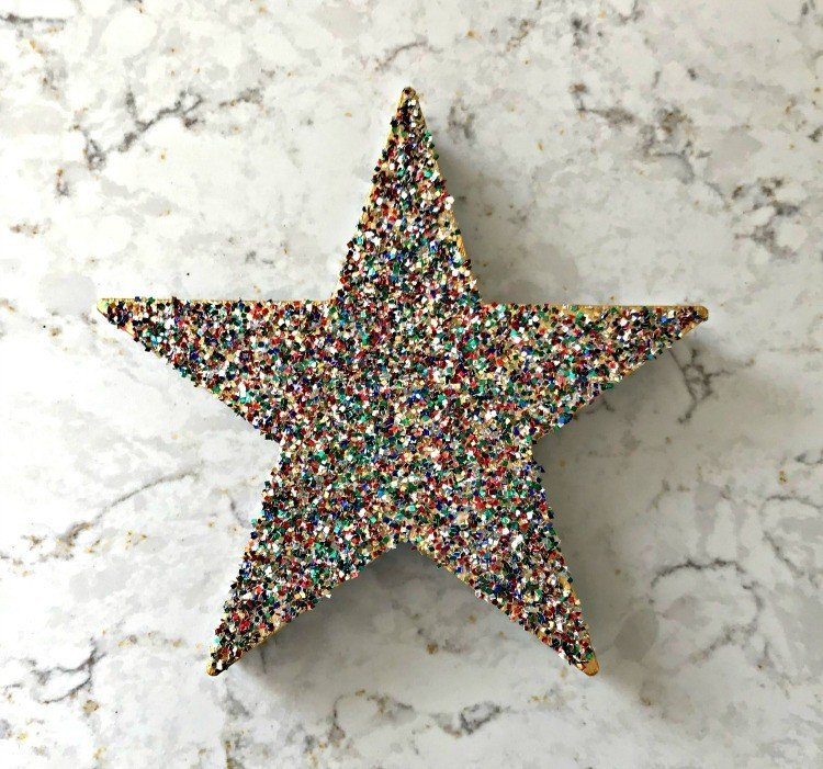 Glitter Star Ornament. Need some new ideas for this years Christmas craft? I've got 12 fun and easy handmade Christmas Ornament Ideas for you! Make 3D scrapbook paper trees, pom pom trees, star string art, unicorn stars, and more. #AbbottsAtHome #Handmade #ChristmasCrafts #ChristmasIdeas #ChristmasOrnaments