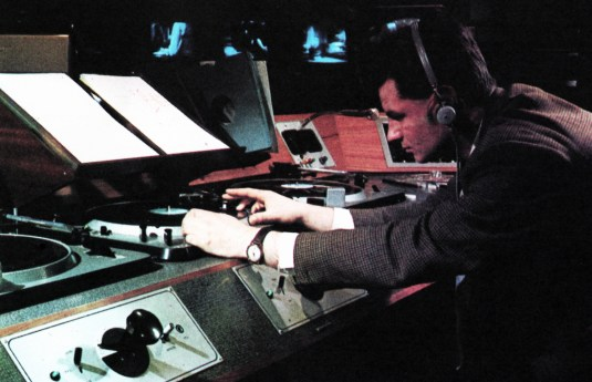 In the right groove: Grams/tape operator aligning pick-up head for exact sound 'feed', on cue. Monitors in background give pre-view of pictures lined up for Director.