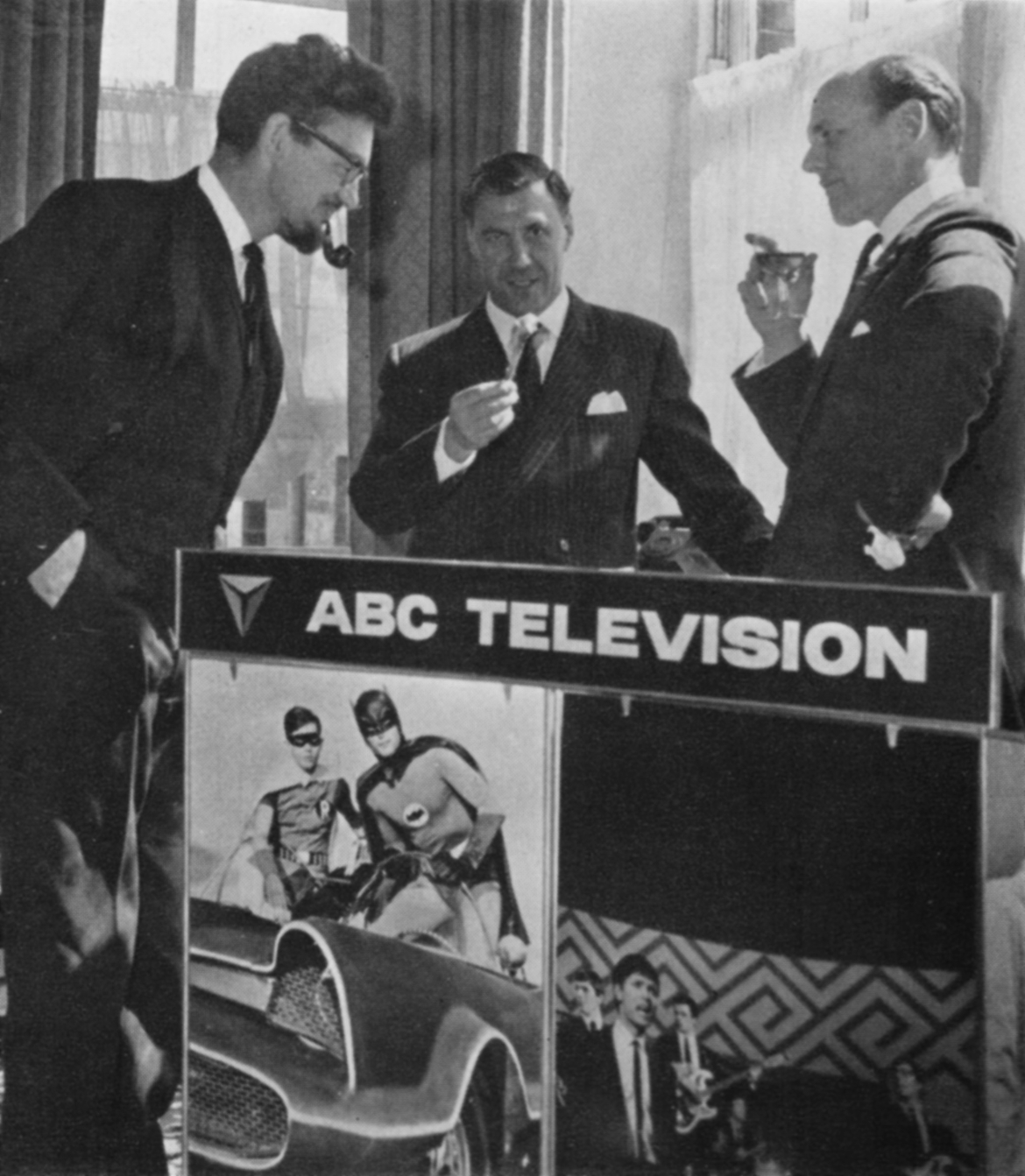 Three men, on drinking, one easting, one smoking a pipe, next to an advertisement for Batman and Thank Your Lucky Stars