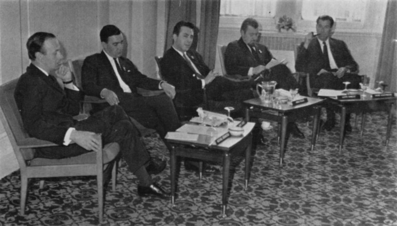 Five men sit in a semicircle