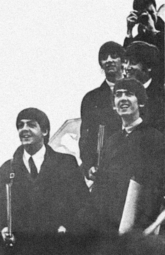 The Beatles on the steps to an aeroplane
