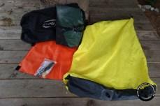 Der Lieferumfang: orange der Sitz, gelb der Befüllsack, schwarz ein Packsack, grün das Boot und Flickzeug. Der Riemen am Packraft gehört nicht zum Lieferumfang