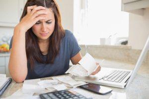 Foto de uma moça com uma mão a cabeça e outra segurando algumas notas fiscais com um notebook a sua frente - manter a sua empresa na informalidade