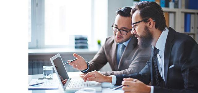Foto de dois empresários olhando para a tela de um notebook, representando os sites para empreendedores
