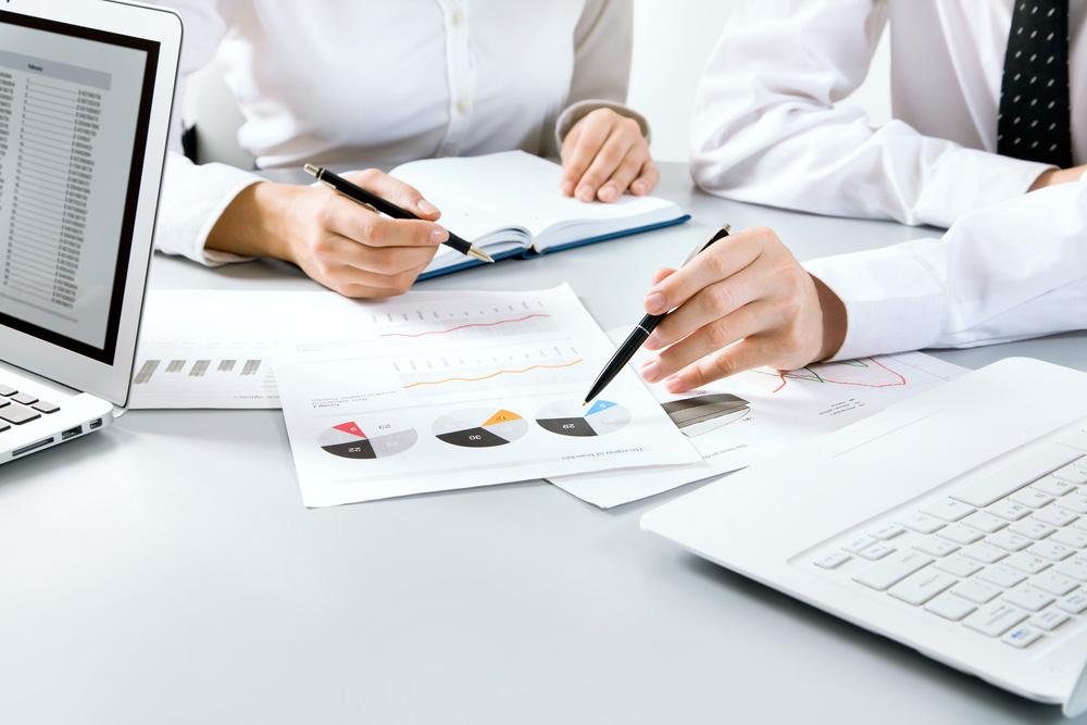 Grupo de pessoas com gráficos sobre a mesa e canetas em mãos