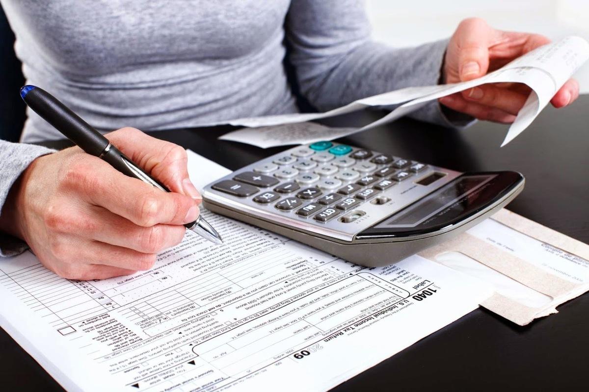 Foto de uma mão escrevendo em um papel e calculando notas, representando o momento de contratar uma contabilidade