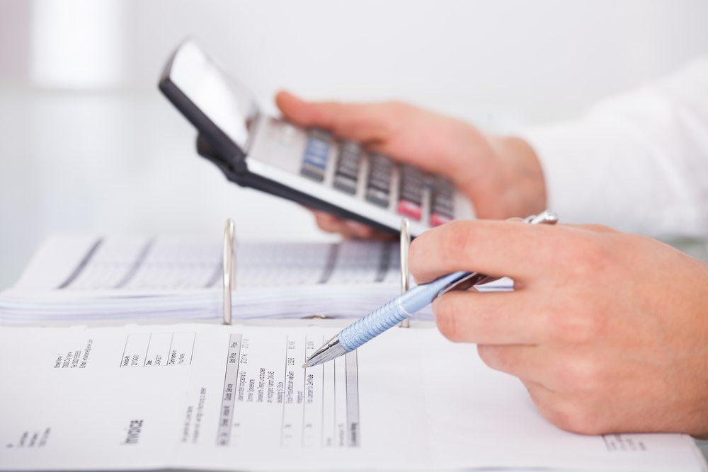 Foto de uma mão masculina com caneta em uma mão e calculadora em outra, representando a hora de trocar a sua contabilidade