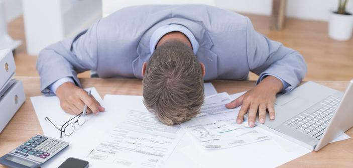 Foto de um homem com a cabeça encostada em mesa com papeis por baixo representando os erros dos novos empreendedores