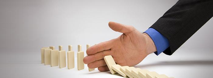 Foto de uma mão segurando uma sequencia de dominós, representando o empreendedorismo na crise econômica