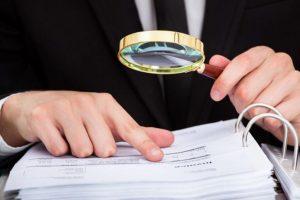 Foto de uma mão masculina segurando uma lupa, indicando para alguns documentos de legalização de empresa