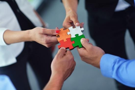 Foto com quatro mãos, cada uma segurando um pedaço de um quebra-cabeça e juntando até formar uma peça grande, representando as estratégias de endomarketing