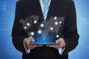 Um rapaz com terno segurando um tablet, representando as novas tecnologias para PMEs