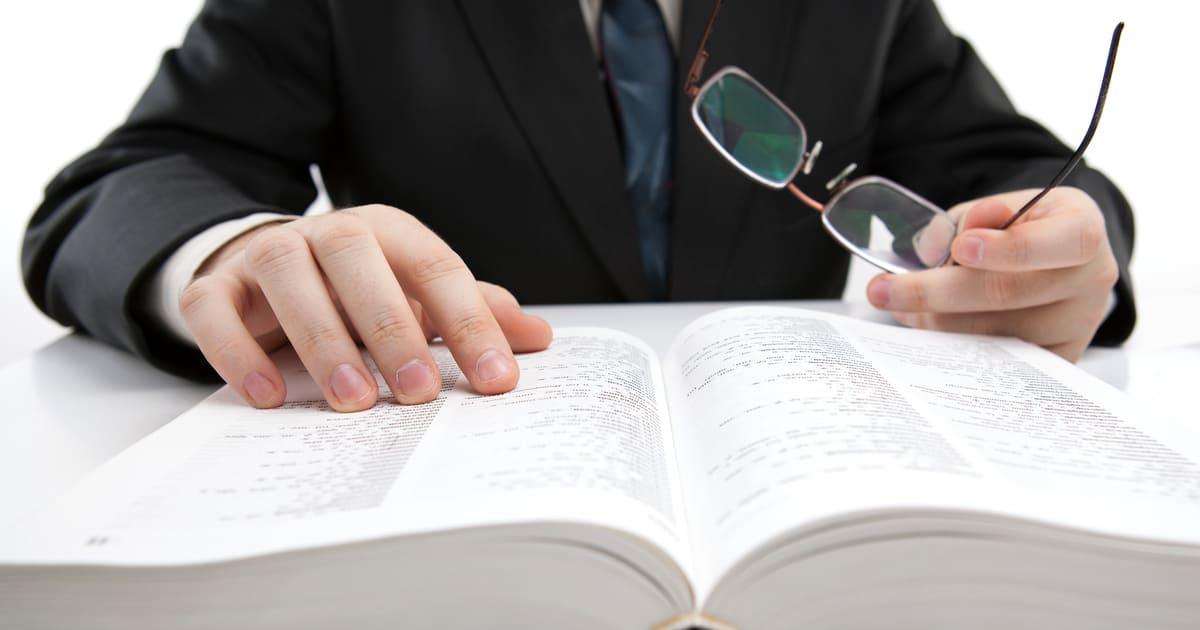 Foto de uma xícara de café com um notebook ao lado e um dicionário, representando os termos contábeis