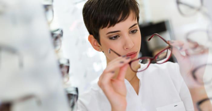 Mulher experimentando um óculos, representando abrir uma ótica - Abertura Simples