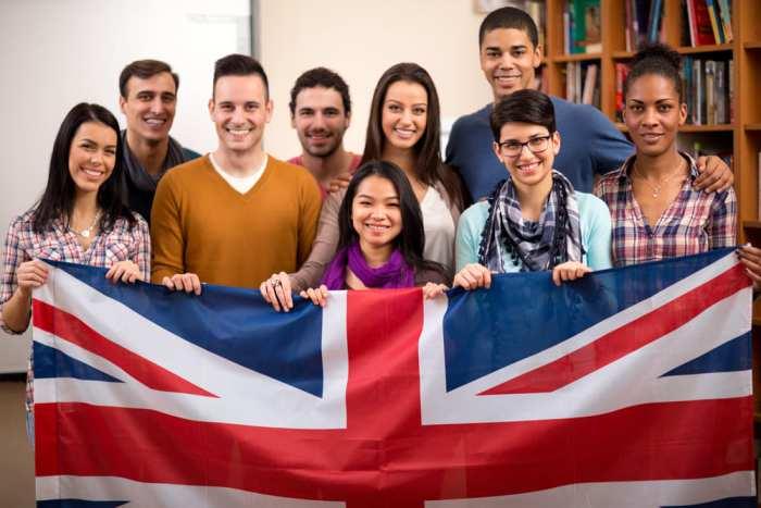 Foto de alguns alunos segurando a bandeira do Reino Unido, representando como abrir uma escola de idiomas