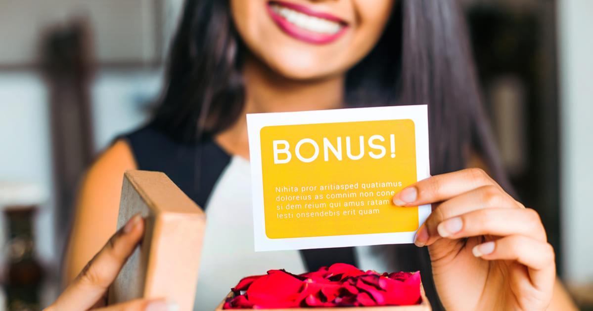 foto de uma mulher sorrindo e mostrando um cartão, representando a bonificação para funcionários