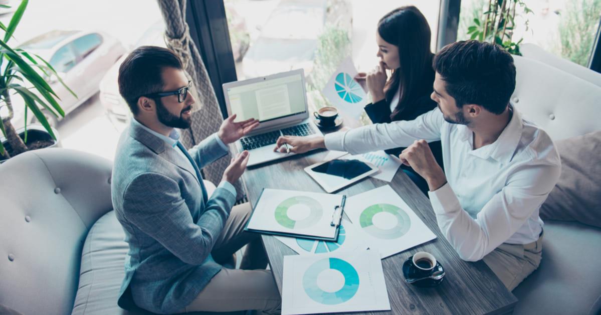foto de um homem apresentando dados para duas pessoas, representando como conseguir investidores