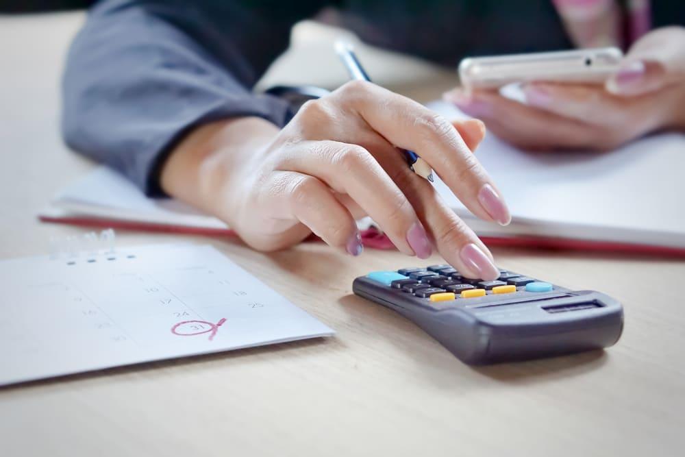 foto de uma mulher digitando em uma calculadora, representando como abrir empresa com nome sujo