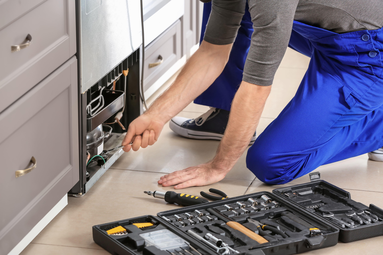 Imagem de um homem fazendo a manutenção do eletrodoméstico depois que viu o post de como montar um serviço de manutenção de eletrodomésticos