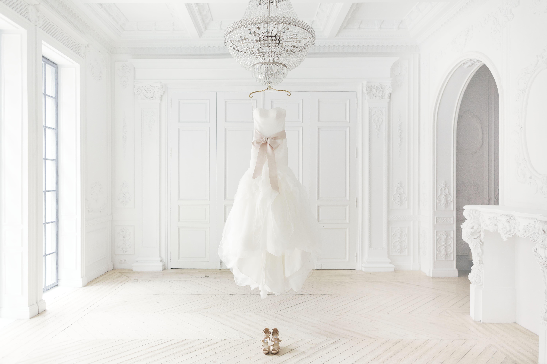 Imagem de um vestido de noiva pendurado no meio de um espaço de um ateliê depois que um empreendedor resolveu abrir uma loja de confecção de vestidos de noiva