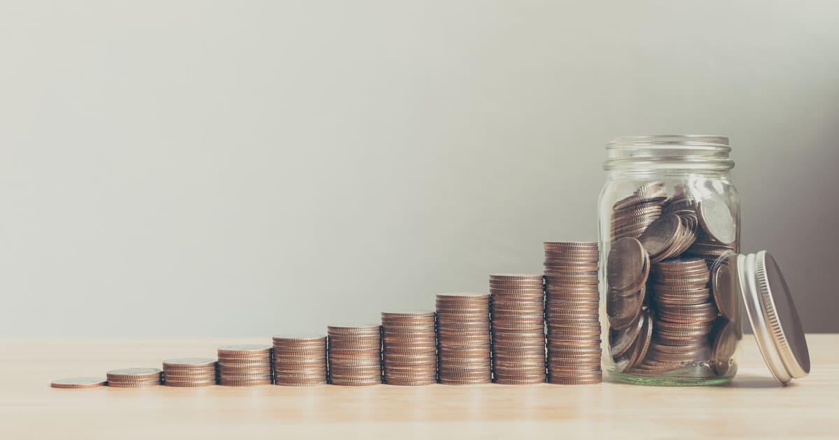 Imagem de algumas moedas em um pote para representar a ajuda financeira que o saque do pagamento do PIS Pasep vai auxiliar as pessoas