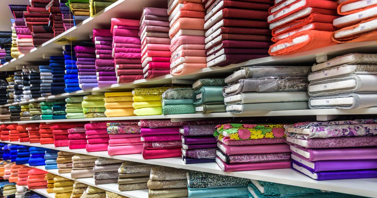 Imagem de algumas prateleiras com tecidos para remeter ao empreendedor que vai abrir uma loja de tecidos