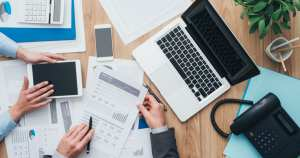 foto vista de cima de pessoas mexendo em papéis e analisando dados, representando como o contador ajuda o empreendedor