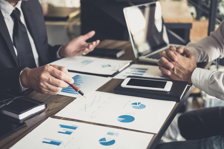 Imagem de alguns empreendedores analisando e pesquisando as principais dúvidas dos investidores iniciantes