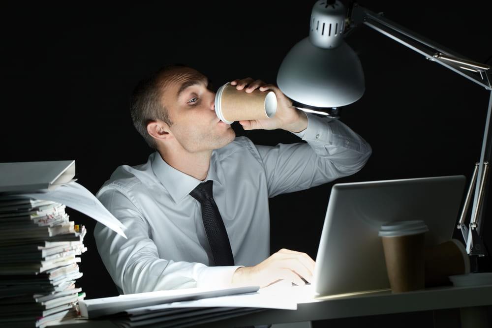 foto de um homem trabalhando a noite com um copo de café, representando como calcular hora extra